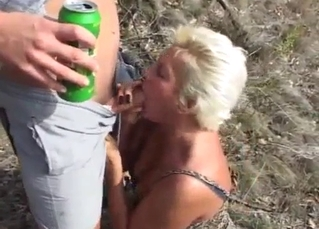 Blonde auntie gives a blowjob under the baking sun